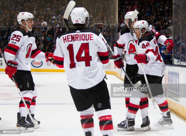 Miles Wood of the New Jersey Devils celebrates his goal on the Toronto Maple Leafs with teammates Jimmy Hayes Adam Henrique and Mirco Mueller during...