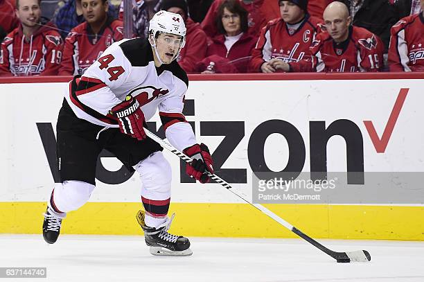 Miles Wood of the New Jersey Devils controls the puck against the Washington Capitals in overtime during a NHL game at Verizon Center on December 29...