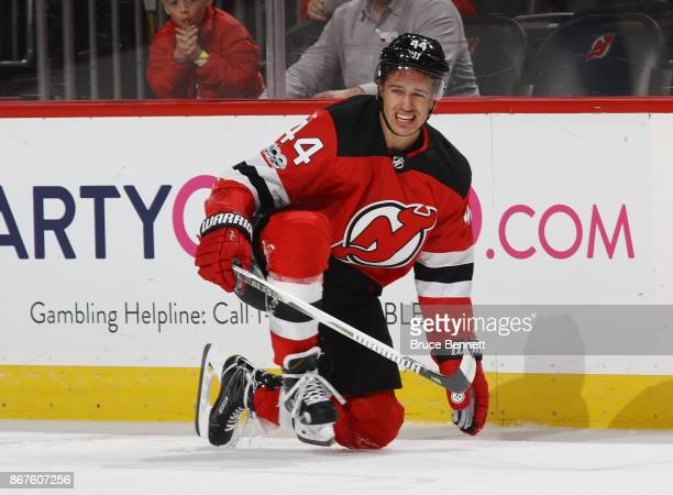 Miles Wood of the New Jersey Devils grimmaces after a first period hit against the Arizona Coyotes at the Prudential Center on October 28 2017 in...