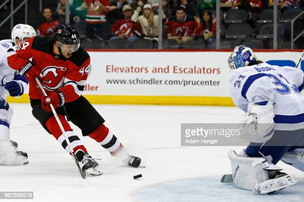 Miles Wood of the New Jersey Devils has his shot stopped by Peter Budaj of the Tampa Bay Lightning during the second period at the Prudential Center...