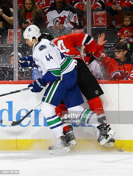 Miles Wood of the New Jersey Devils is checked into the boards by Erik Gudbranson of the Vancouver Canucks during the game at Prudential Center on...