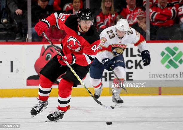 Miles Wood of the New Jersey Devils takes the puck as Connor Brickley of the Florida Panthers defends in the second period on November 11 2017 at...