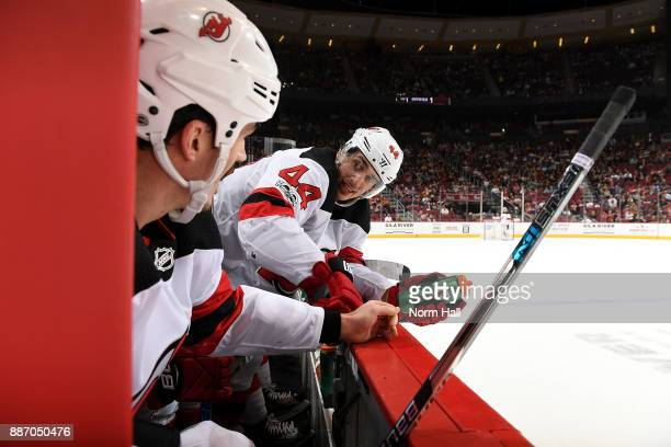 Miles Wood of the New Jersey Devils talks with teammate Brian Boyle while on the bench during a game against the Arizona Coyotes at Gila River Arena...