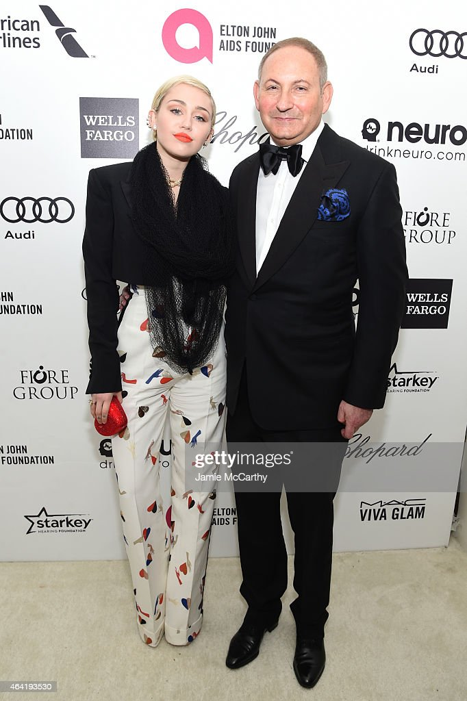 Miley Cyrus and John Demsey Group President The Estée Lauder Companies Inc attend the 23rd Annual Elton John AIDS Foundation Academy Awards Viewing...