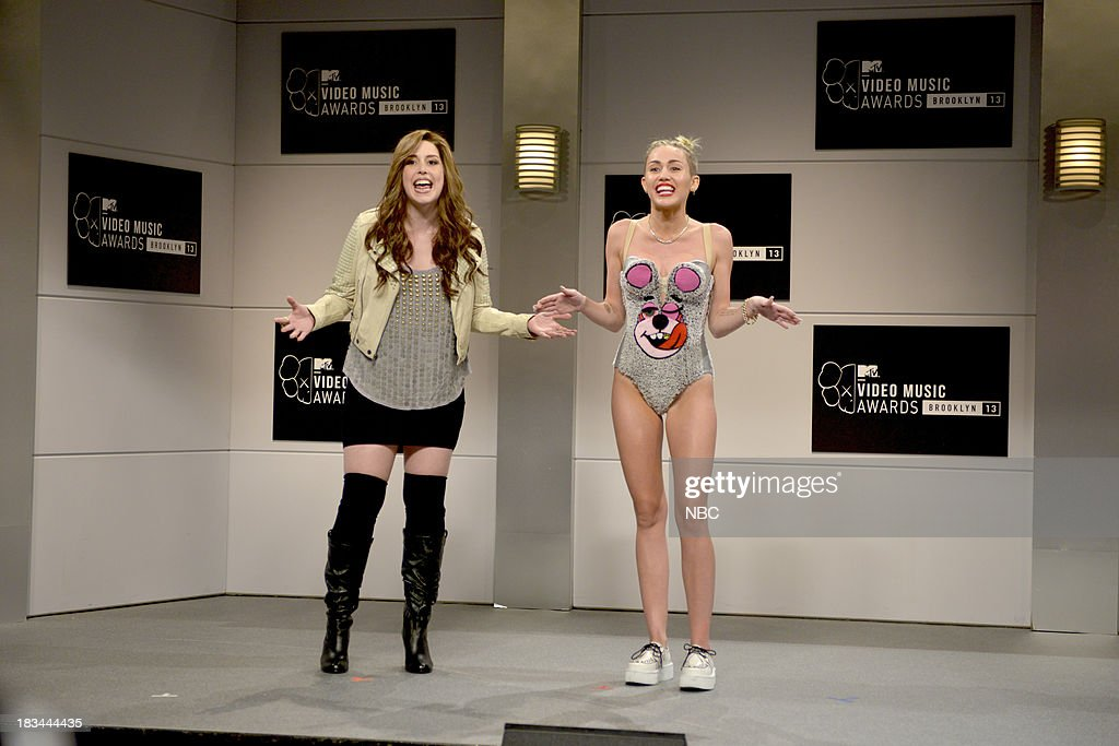 LIVE -- 'Miley Cyrus' Episode 1643 -- Pictured: (l-r) Vanessa Bayer as future Miley Cyrus, Miley Cyrus as herself during the 'New York City, 2045' opening sketch --