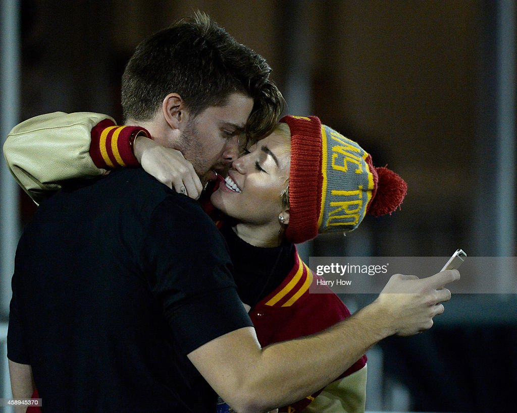 Miley Cyrus kisses Patrick Schwarzenegger during the game between the California Golden Bears and the USC Trojans at Los Angeles Memorial Coliseum on...
