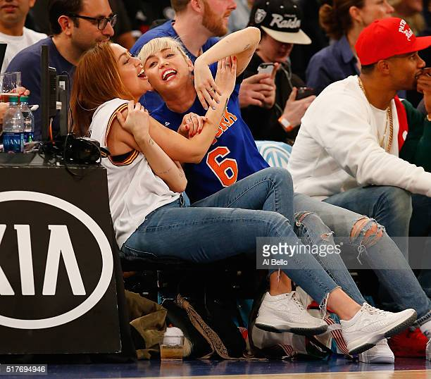 Miley Cyrus looks on with her sister Brandi during the game between the New York Knicks and the Cleveland Cavaliers at Madison Square Garden on March...