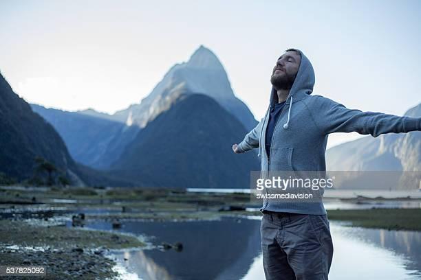 Milford Sound : Jeune homme bras tendus