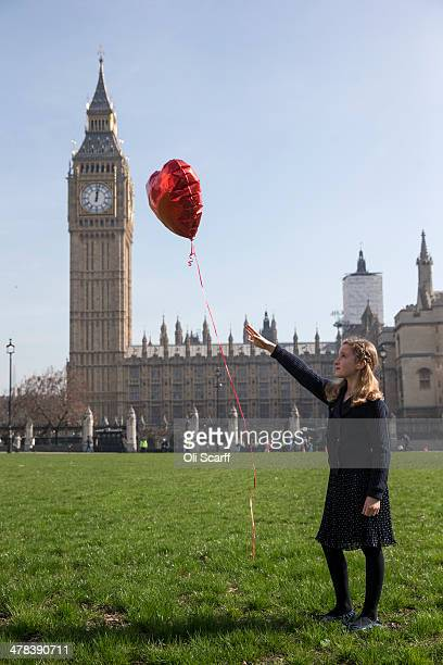Milie aged 9 releases a red heartshaped balloon in Parliament Square in front of the Houses of Parliament as a symbolic marking of the third...
