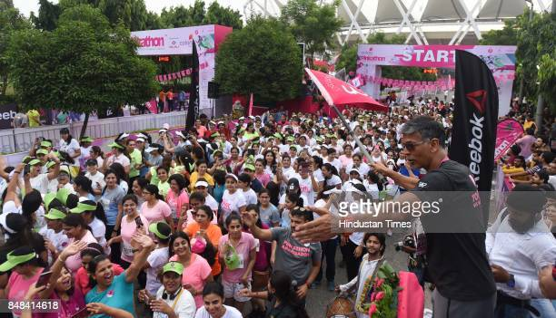 Milind Soman model and actor and women athletes participate during the Pinkathon run India's biggest women run at Jawahar Lal Nehru Stadium on...