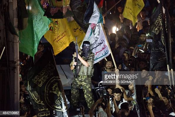 A militant brandishes his weapon as he fires rounds into the air after joining hundreds of Gazans gathered at an intersecition in Gaza City on August...