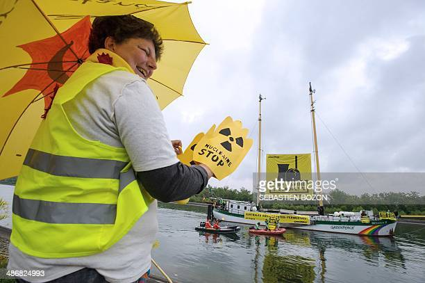A militant for the Fessenheim nuclear powerplant closing salutes environmental group Greenpeace activists who hold from their Beluga II boat a banner...