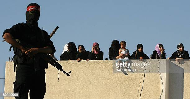 A militant stands guard as Palestinian women and a child observe a rally in support of the Islamic Jihad from the rooftop of a building in the Khan...
