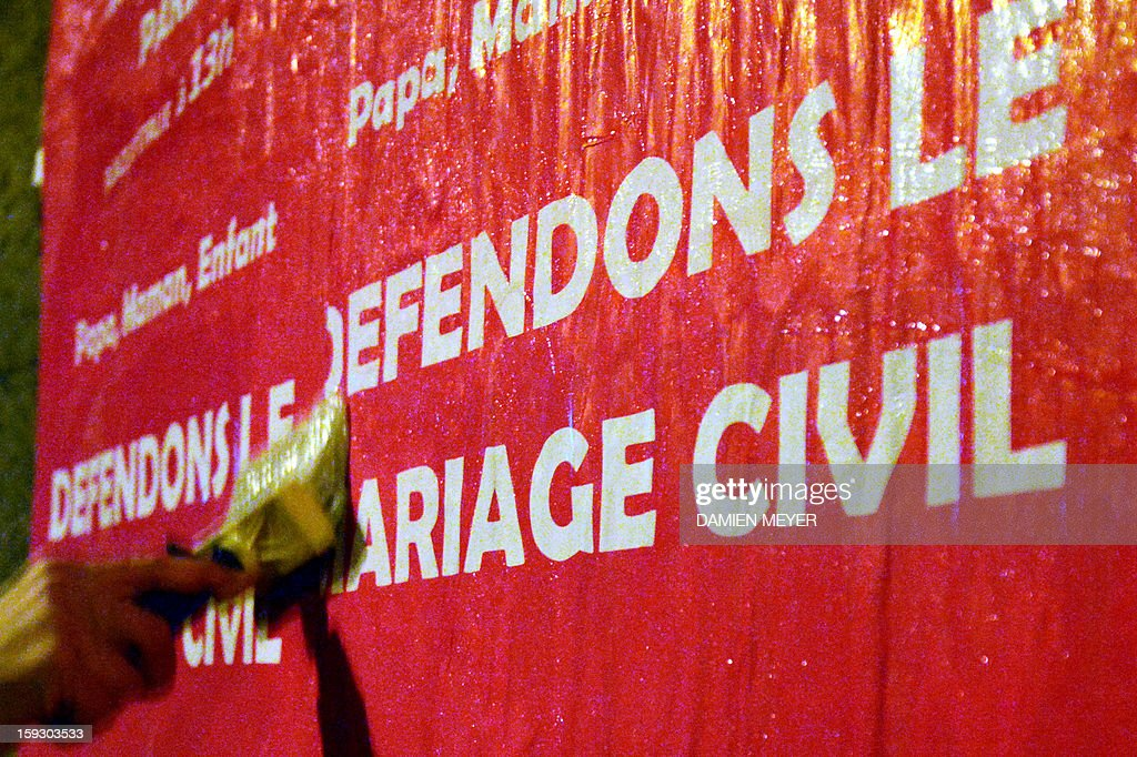 A militant sticks on January 11, 2013 posters on a billboard in the French western city of Nantes, advertising for the national demonstration to be held in Paris on January 13 against the legalisation of gay marriage. Plans by France's Socialist government to extend marriage and adoption rights to gay couples have proven deeply divisive, igniting fierce protests from opponents including Catholic and Muslim leaders, with a new mass rally planned in Paris for January 13. Poster reads 'Let's protect the civil marriage'.