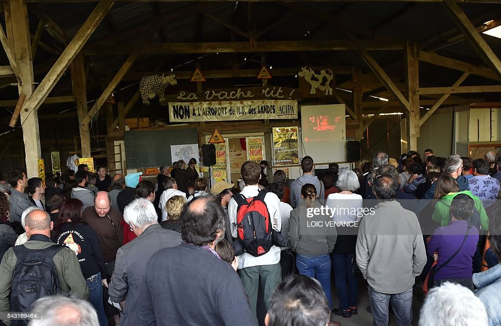Militants against the Notre-Dame-des-Landes airport listen to the results at the Vache rit farm after a local referendum organised in Loire Atlantique to transfer of the Nantes Atlantique airport to Notre-Dame-des-Landes, in Notre-Dame-des-Landes, on June 26, 2016. Nearly one million people living in France's Loire-Atlantique department voted in a referendum which poses the question 'Are you in favour of the project to transfer the Nantes-Atlantique airport to the municipality of Notre-Dame-des-Landes?' to voters. The referendum was organised by the French executive power hoping to find a solution to the issue which has dragged on for 50 years. / AFP / LOIC
