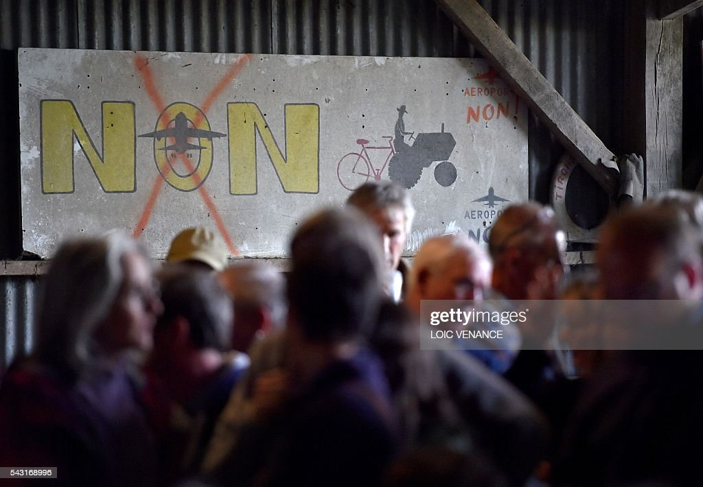 Militants against the Notre-Dame-des-Landes airport react as they listen to the results at the Vache rit farm after a local referendum organised in Loire Atlantique to transfer of the Nantes Atlantique airport to Notre-Dame-des-Landes, in Notre-Dame-des-Landes, on June 26, 2016. Nearly one million people living in France's Loire-Atlantique department voted in a referendum which poses the question 'Are you in favour of the project to transfer the Nantes-Atlantique airport to the municipality of Notre-Dame-des-Landes?' to voters. The referendum was organised by the French executive power hoping to find a solution to the issue which has dragged on for 50 years. / AFP / LOIC