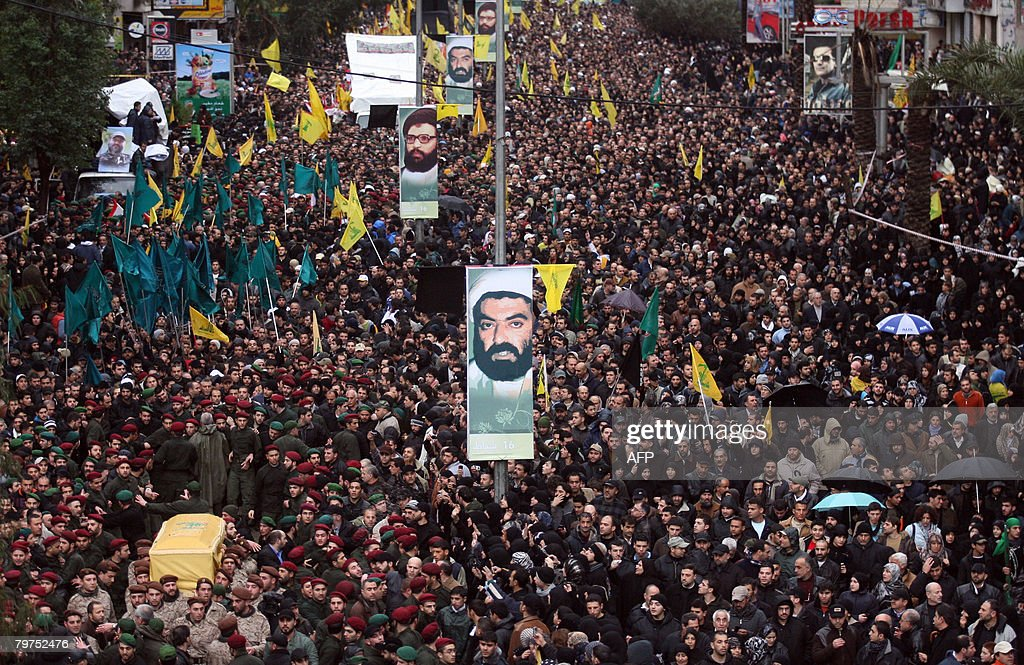Militants carry the coffin of slain top Hezbollah commander Imad Mughnieh past posters of Hezbollah leaders allegedly slain by Israel during his...
