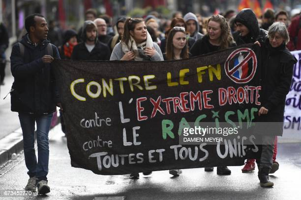 Militants hold a banner 'against FN farright racism' as they demonstrate against the farright party National Front qualified for the second round of...
