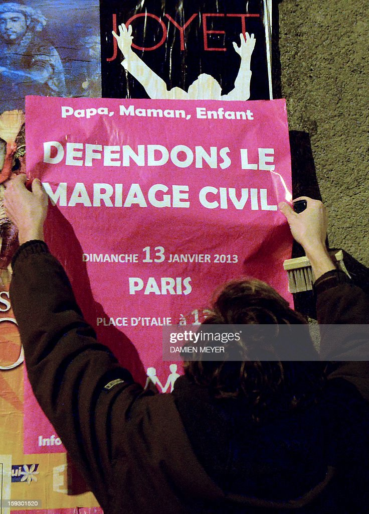 Militants stick on January 11, 2013 posters on a billboard in the French western city of Nantes, advertising for the national demonstration to be held in Paris on January 13 against the legalisation of gay marriage. Plans by France's Socialist government to extend marriage and adoption rights to gay couples have proven deeply divisive, igniting fierce protests from opponents including Catholic and Muslim leaders, with a new mass rally planned in Paris for January 13. Poster reads 'Let's protect the civil marriage'. AFP PHOTO / DAMIEN MEYER