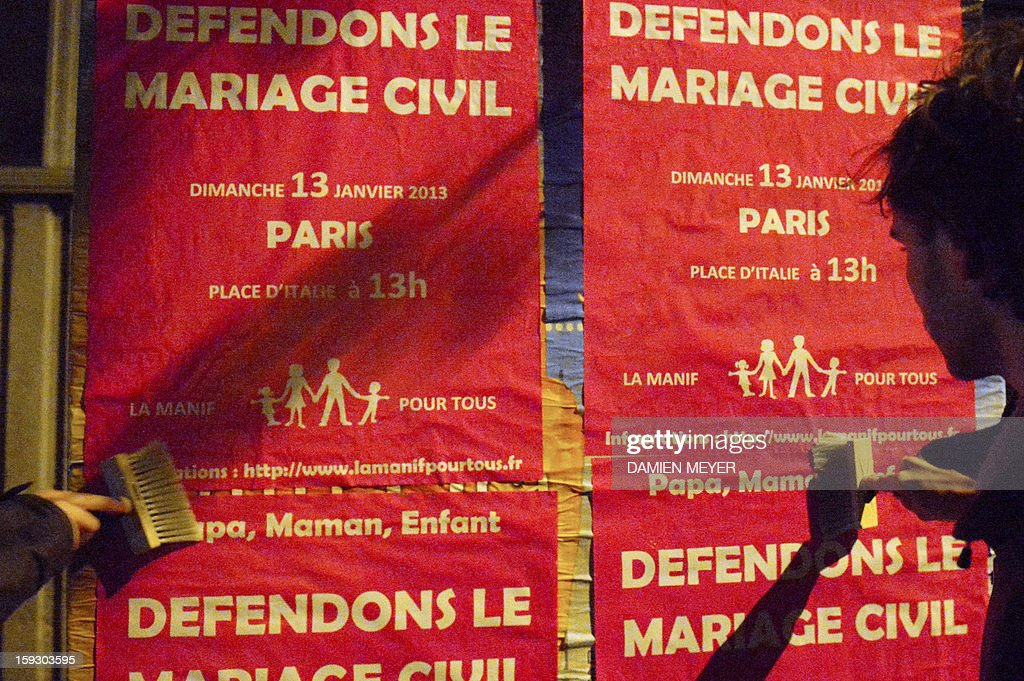 Militants stick on January 11, 2013 posters on a billboard in the French western city of Nantes, advertising for the national demonstration to be held in Paris on January 13 against the legalisation of gay marriage. Plans by France's Socialist government to extend marriage and adoption rights to gay couples have proven deeply divisive, igniting fierce protests from opponents including Catholic and Muslim leaders, with a new mass rally planned in Paris for January 13. Poster reads 'Let's protect the civil marriage'.