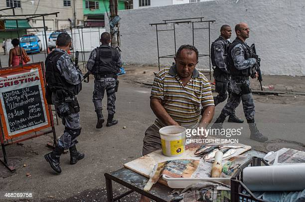 PM militarized police commandos keep guard at a checkpoint during a security operation at Praia da Ramos and Roquette Pinto communities part of the...