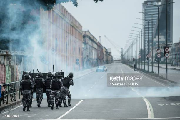 TOPSHOT PM militarized police personnel in riot gear fire tear gas at protestors blocking the road before the longdistance bus terminal during the...