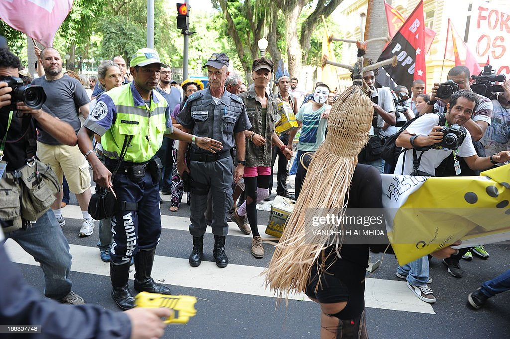 A militarized policeman (L) aims a taser gun at one of the ctivists protesting in front of the Guanabara state government's palace against the privatization of the Mario Filho 'Maracana' stadium in Rio de Janeiro, Brazil, on April 11, 2013. Bidding for the privatization of Rio's iconic Maracana stadium was to go ahead as planned Thursday after a local court rejected an appeal to block the process. Maracana, which was built for the 1950 World Cup, is undergoing extensive renovation at a cost of 430 million dollars to host four Confederations Cup matches in June as well as seven World Cup games next year, including the finals of both tournaments. AFP PHOTO /VANDERLEI ALMEIDA