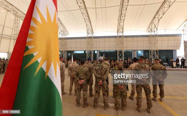Military advisers from the international coalition forces stand during a transfer of authority ceremony on June 15 at the Kurdistan Training...