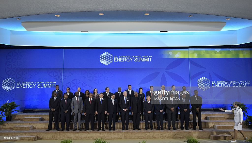 A military aide directes US Vice President Joe Biden and Caribbean heads of delegations after posing for a group photo during the US, Caribbean, Central American Energy Summit in the Dean Acheson Auditorium of the State Department in Washington, DC on May 4, 2016. / AFP / MANDEL