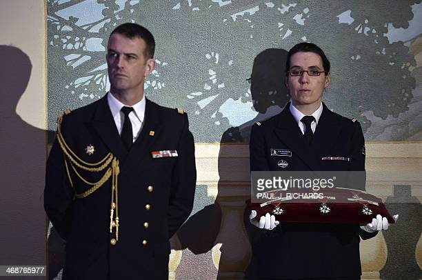 Military aides wait with six medals of the French Legion of Honor as French President Francois Hollande addresses the audience February 11 at the Ft...