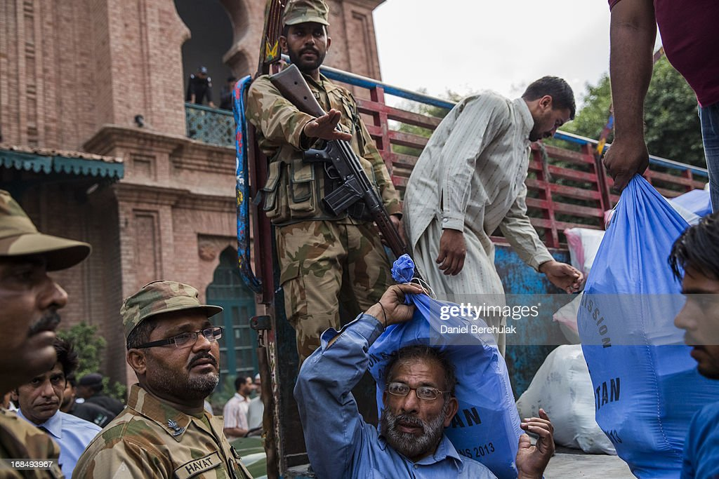 Military and police personnel oversee the delivery and unloading of ballot boxes and papers on May 10, 2013 in Lahore, Pakistan. Pakistan's parliamentary elections are due to be held on May 11. It is the first time in the country's history that an elected government will hand over power to another elected government.