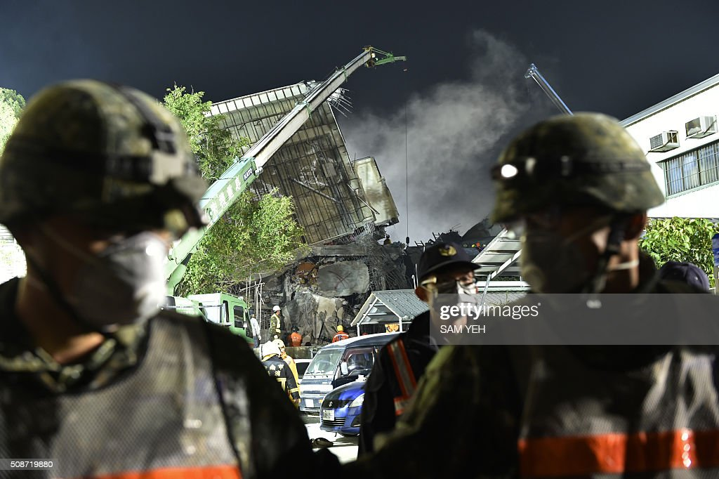 Military (foreground) and rescue personnel work at the site of a collapsed building in the southern Taiwanese city of Tainan on February 6, 2016 following a strong 6.4-magnitude earthquake. A powerful earthquake in Taiwan felled a 16-storey apartment complex full of families who had gathered for Lunar New Year celebrations in the early hours of February 6, with at least seven dead and more than 30 feared trapped. AFP PHOTO / Sam Yeh / AFP / SAM YEH