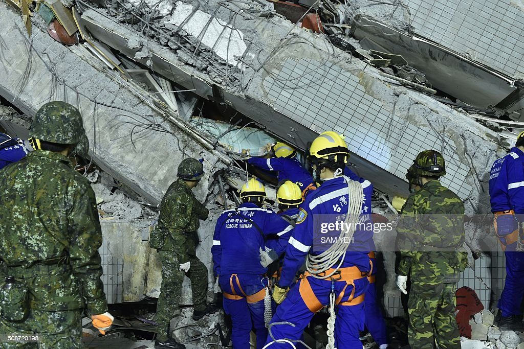 Military and rescue personnel work at the site of a collapsed building in the southern Taiwanese city of Tainan on February 6, 2016 following a strong 6.4-magnitude earthquake. A powerful earthquake in Taiwan felled a 16-storey apartment complex full of families who had gathered for Lunar New Year celebrations in the early hours of February 6, with at least seven dead and more than 30 feared trapped. AFP PHOTO / Sam Yeh / AFP / SAM YEH