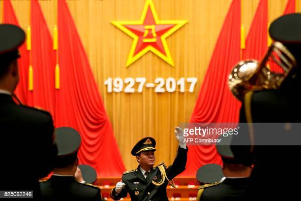 A military band conductor rehearses ahead a ceremony to commemorate the 90th anniversary of the founding of the People's Liberation Army at the Great...