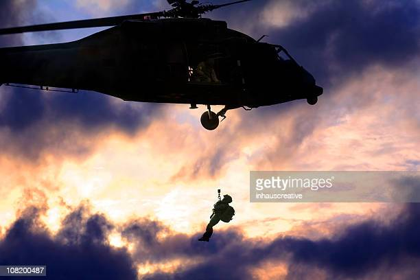 Military blackhawk helicopter rescuing a soldier