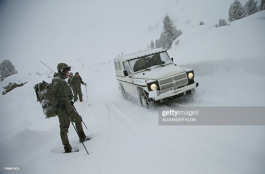 A military car is seen driving in the snow as Austrian armed forces from the 6th Infantry Brigade (6. Jaegerbrigade), of the 2nd Engineer Battalion Salzburg (Pionierbatallion 2), practice an alpine training winter exercise (above 2000m altitude) during a foggy and snowy day in the Tuxer mountains near Wattens on January 16, 2013. Austrians will decide on Sunday whether to maintain compulsory military service or switch to a professional army in a referendum that has split the small, neutral country. AFP PHOTO / ALEXANDER KLEIN