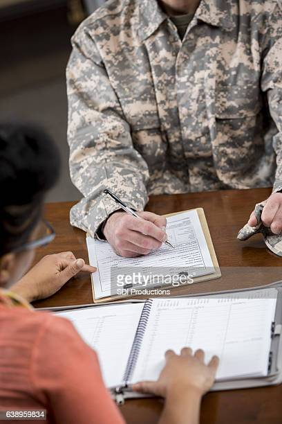 Military counselor assists soldier in new patient paperwork