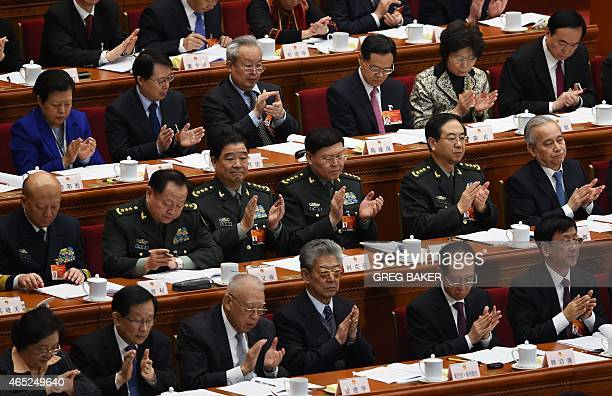 Military delegates applaud a speech by Chinese Premier Li Keqiang during the opening session of the National People's Congress in the Great Hall of...