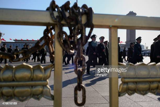 Military delegates from the Chinese People's Liberation Army walk towards the Great Hall of the People for a plenary meeting of the National People's...