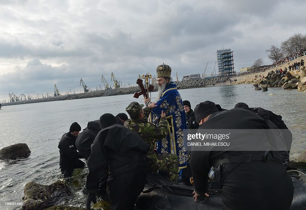 Military divers help a Romanian priest to get on a rubber boat as he prepares to throw a wooden cross in the Black Sea during an epiphany religious service in Constanta city (230km east from Bucharest), on January 6, 2013. Thousands romanian Orthodox believers attended the celebration of Epiphany in the Black Sea coastal city.