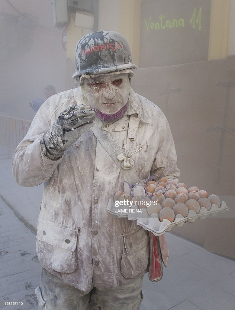 A military dressed man holding eggs takes part in the battle of 'Enfarinats', a floor fight in the town of Ibi, in the south-eastern Spain on December 28, 2012. For 200 years Ibi's citizens annually celebrate with a battle using flour, eggs and firecrackers outside the city townhall.