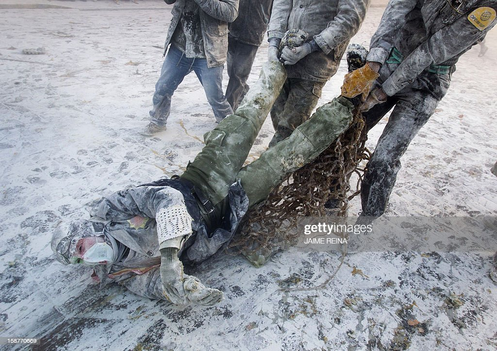 A military dressed man is pulled by other as they take part in the battle of 'Enfarinats', a floor fight in the town of Ibi, in the south-eastern Spain on December 28, 2012. For 200 years Ibi's citizens annually celebrate with a battle using flour, eggs and firecrackers outside the city townhall.