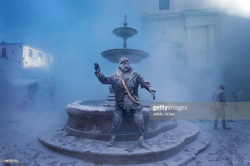 A military dressed man throws an egg as he takes part in the battle of 'Enfarinats', a floor fight in the town of Ibi, in the south-eastern Spain on December 28, 2012. For 200 years Ibi's citizens annually celebrate with a battle using flour, eggs and firecrackers outside the city townhall.