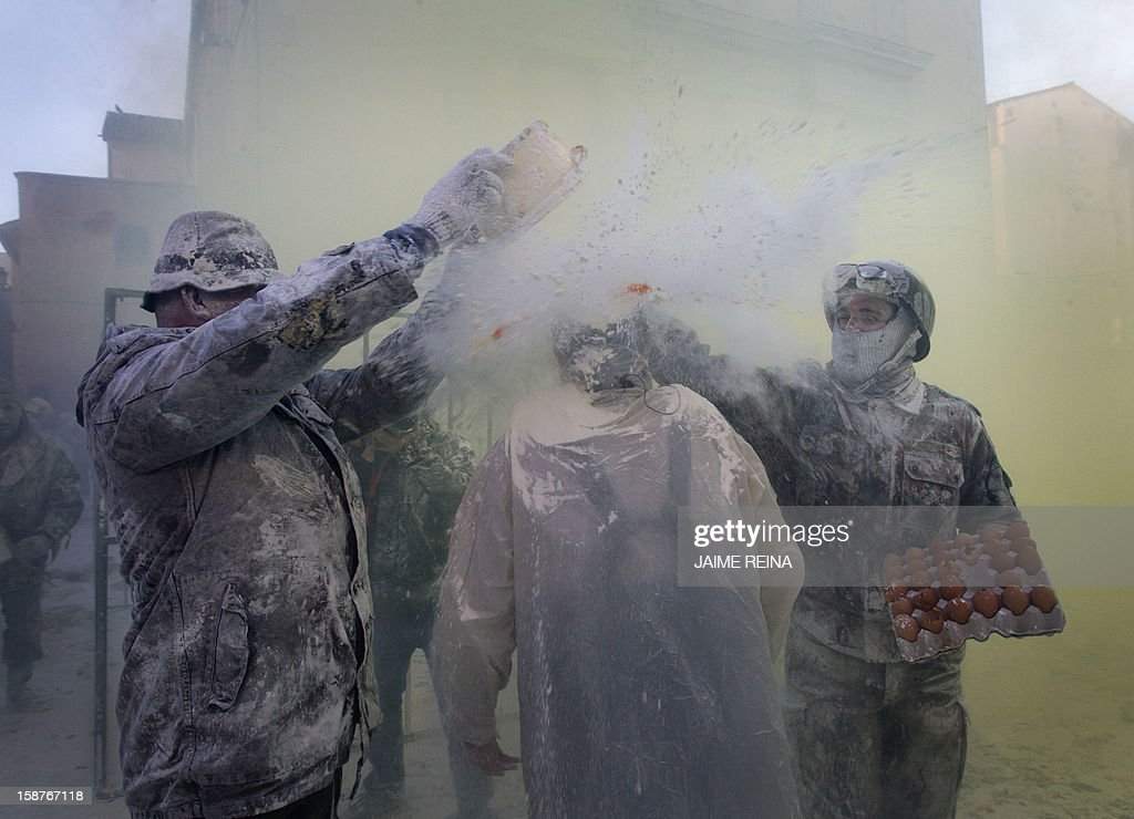 Military dressed men smashes eggs on the head of a man as they take part in the battle of 'Enfarinats', a floor fight in the town of Ibi, in the south-eastern Spain on December 28, 2012. For 200 years Ibi's citizens annually celebrate with a battle using flour, eggs and firecrackers outside the city townhall.