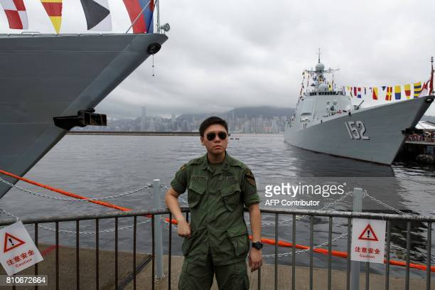 A military enthusiast visitor clad in historic US Army uniform poses beside the Chinese People's Liberation Army Navy destroyers Yinchuan and Jinan...
