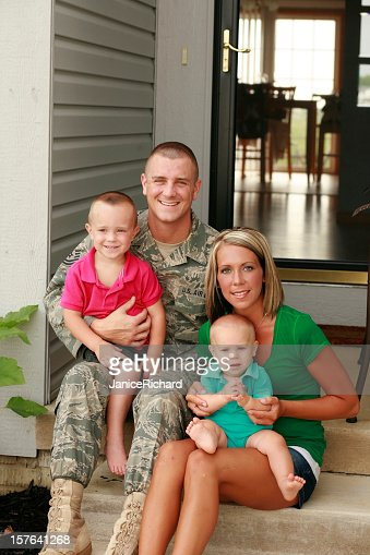 A military family of four sitting out on their front steps