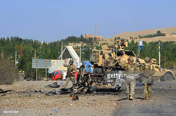 US military forces walk at the wreckage of a car bomb near the US consulate after an attack in Herat on September 13 2013 Seven heavily armed Taliban...
