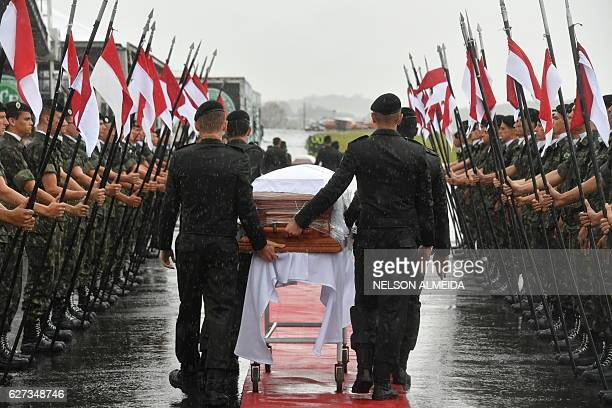 TOPSHOT A military guard of honor receives the coffins of the members of the Chapecoense Real football club team killed in a plane crash in Colombia...