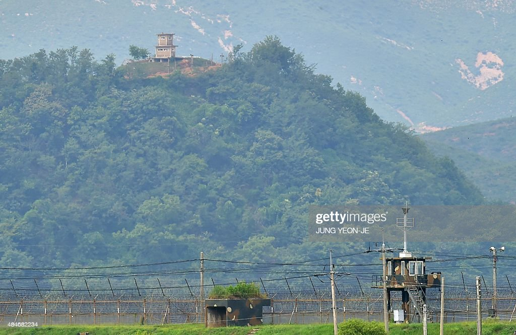 Military guard posts of South Korea (bottom) and North Korea (top) stand opposite each other as seen from in the border city of Paju on August 21, 2015. North Korean leader Kim Jong-Un ordered his frontline troops onto a war-footing from August 21, as military tensions with South Korea soared following a rare exchange of artillery shells across their heavily fortified border. AFP PHOTO / JUNG YEON-JE