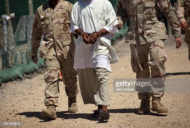 US military guards move a detainee inside the American detention center for 'enemy combatants' on September 16 2010 in Guantanamo Bay Cuba With...